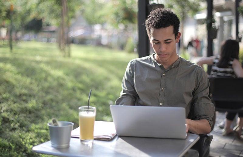focused black male freelancer using laptop in street cafe 3799115